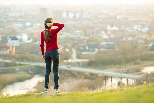 街の景色を楽しみながら屋外に立っている若い女性。リラックス、自由、ウェルネスのコンセプト。