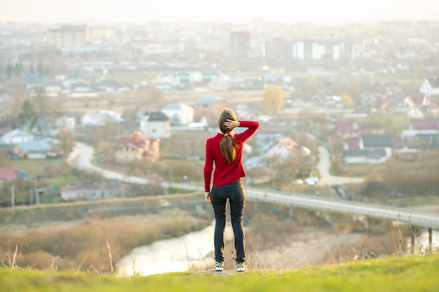 Young woman standing outdoors enjoying city view. relaxing, freedom and wellness concept.