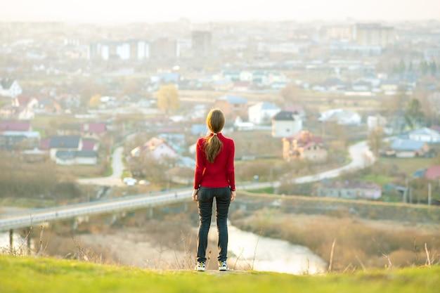 街の景色を楽しみながら屋外に立っている若い女性