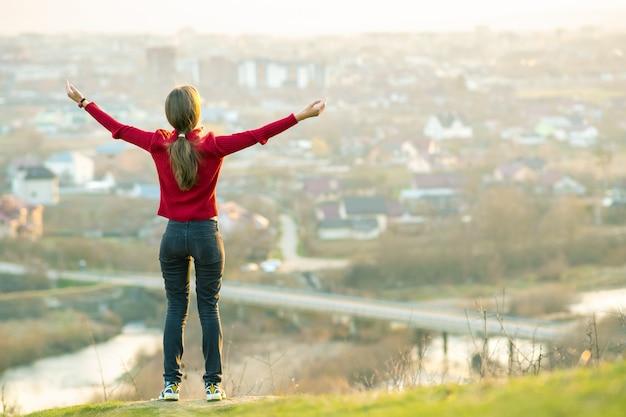 Молодая женщина стоя outdoors поднимая ее руки наслаждаясь видом на город. расслабляющий, свобода и оздоровительный концепции.