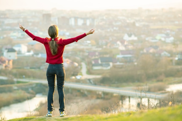Young woman standing outdoors raising her hands enjoying city view. relaxing, freedom and wellness concept.