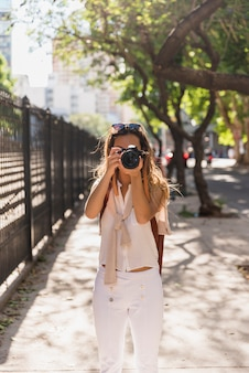 Young woman standing in the park taking photo from camera