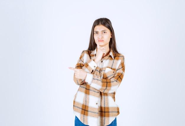 Giovane donna in piedi e che indica al suo fianco sul muro bianco.