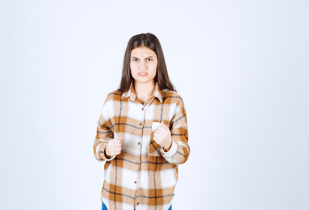 Young woman standing and posing on white wall.