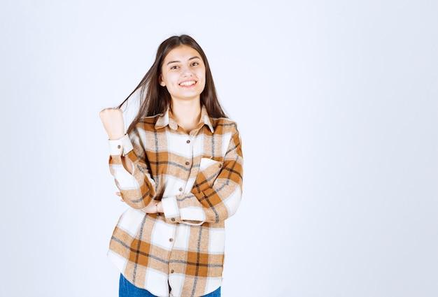 Giovane donna in piedi e in posa sul muro bianco.