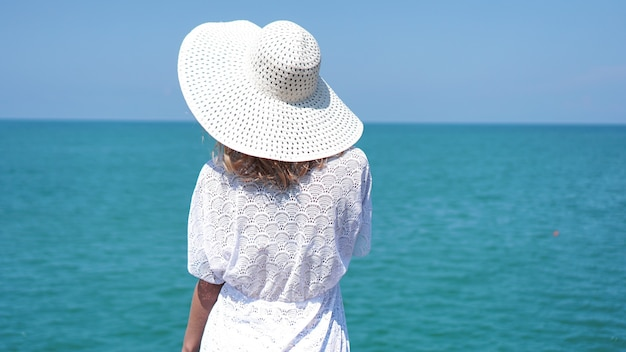 Young woman standing on sand near sea and holding a white hat