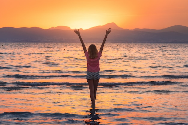 Young woman standing in sea with waves on sandy beach against mountains and orange sky at sunset in summer