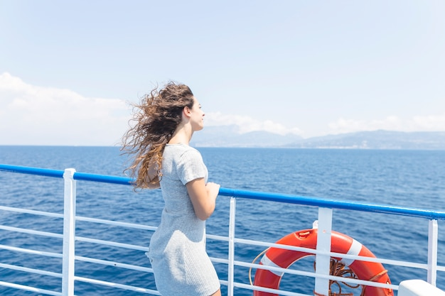 Young woman standing next to the ship's handrail looking at the blue sea