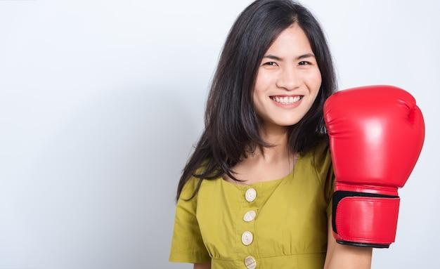 Улыбка молодой женщины стоя в боксерских перчатках