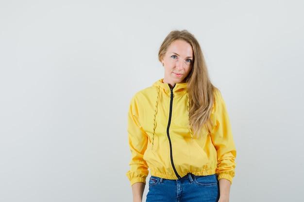 まっすぐ立って、黄色のボンバージャケットとブルージーンズでカメラに向かってポーズをとって、魅力的に見える、正面図。