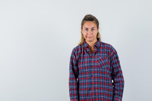 Молодая женщина стоит прямо и позирует спереди в клетчатой рубашке и выглядит красиво