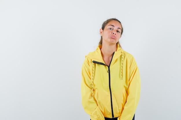 まっすぐ立って、黄色のボンバージャケットと黒のズボンで正面にポーズをとって真剣に見える若い女性