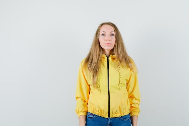 まっすぐ立って、黄色のボンバージャケットとブルージーンズでカメラに向かってポーズをとって、楽観的な正面図を探している若い女性。