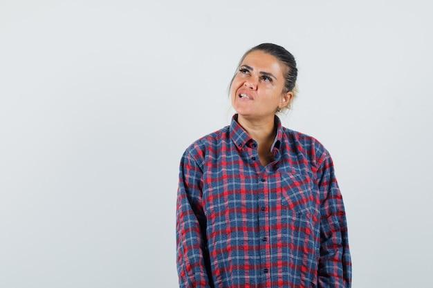 Giovane donna in piedi dritta, smorfie in camicia a quadri e guardando pensieroso, vista frontale.