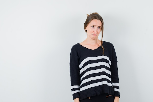 Young woman standing straight and looking at right in striped knitwear and black pants and looking dismal