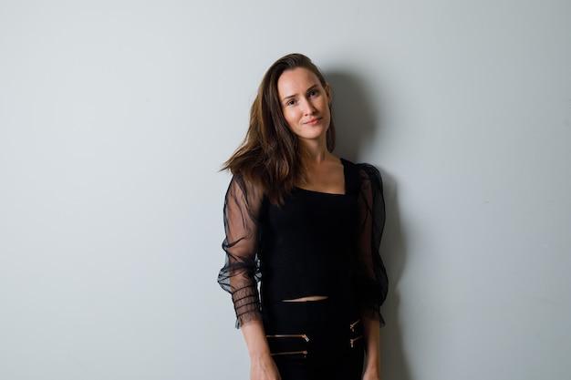 Giovane donna in piedi dritta e in posa davanti in camicetta nera e pantaloni neri e sembra attraente