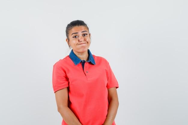 Giovane donna in piedi dritto e sbuffando le guance in maglietta rossa e guardando divertente. vista frontale.