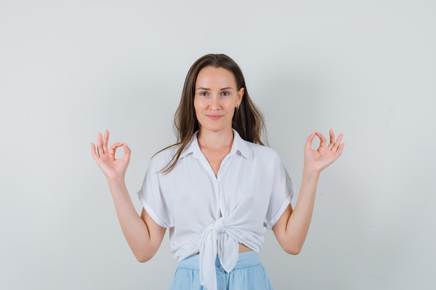 まっすぐ立って、白いブラウスと水色のスカートで両手でokの兆候を示し、自信を持って見える若い女性