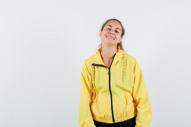 まっすぐ立って、笑顔で、黄色のボンバージャケットと黒のズボンでカメラに向かってポーズをとって、かわいく見える若い女性