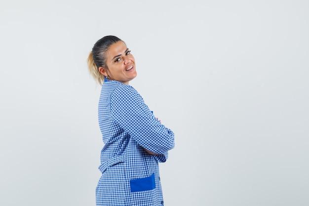 Giovane donna in piedi dritto mentre guarda sopra la spalla in camicia del pigiama a quadretti blu e sembra carina, vista frontale.