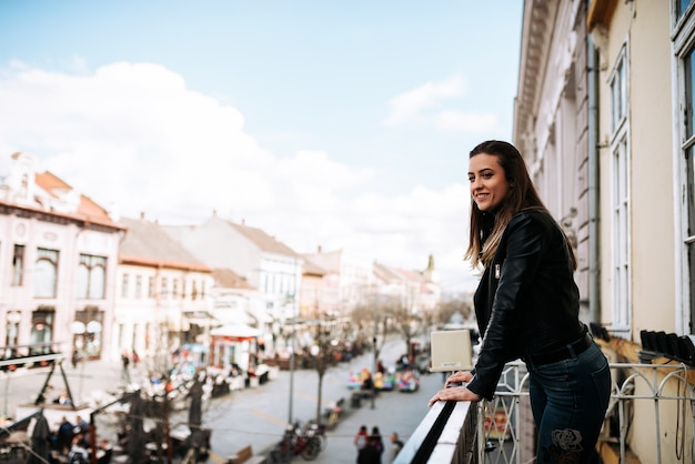 Young woman standing on a terrace over the city street.