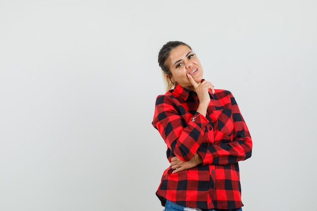 Young woman standing in thinking pose in checked shirt, shorts and looking sensible. front view.
