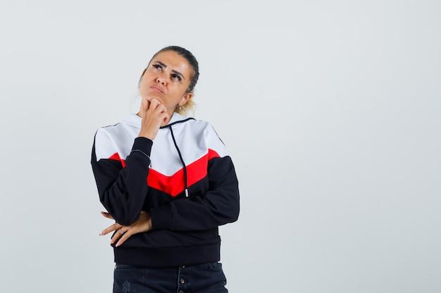 Giovane donna in piedi nella posa di pensiero, mettendo la mano sotto il mento in maglione e jeans neri e guardando pensieroso. vista frontale.