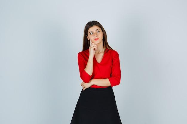 Giovane donna in piedi nella posa di pensiero, mettendo il dito indice sotto il mento in camicetta rossa