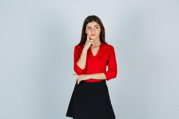 Giovane donna in piedi nella posa di pensiero, mettendo il dito indice sul mento