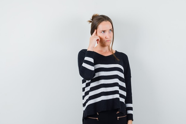 Young woman standing in thinking pose in striped knitwear and black pants and looking pensive