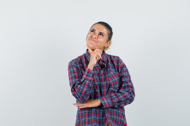 Giovane donna in piedi nella posa di pensiero mentre mette il dito indice sul mento in camicia a quadri e guardando pensieroso, vista frontale.