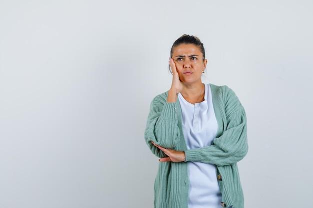 Giovane donna in piedi in posa di pensiero in camicia bianca e cardigan verde menta e guardando pensierosa