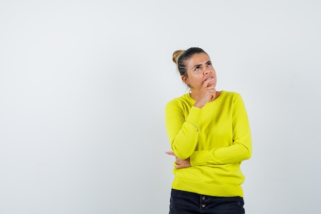 Giovane donna in piedi in posa di pensiero in maglione giallo e pantaloni neri e guardando pensierosa