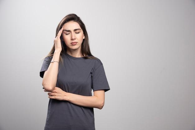 Giovane donna in piedi e tocca la testa per il dolore