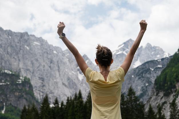 彼女の腕を高く上げて美しいロッキー山脈の下に立っている若い女性。