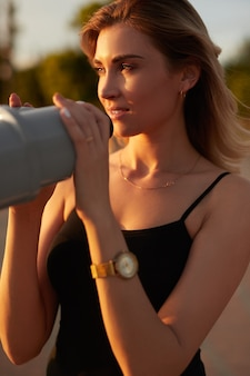 Young woman standing on viewpoint with binoculars in sunlight