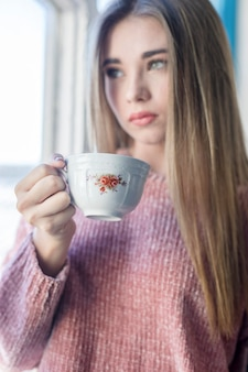 Young woman standing next to a window while holding a cup of tea