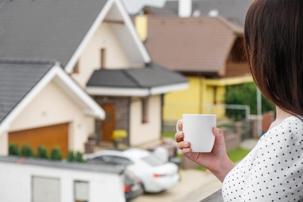 白いカップを手に立って、現代の家を見ている若い女性。夢の家の建設。建築会社の広告コンセプト。良い近所