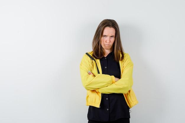 腕を組んで立っていると失望している若い女性