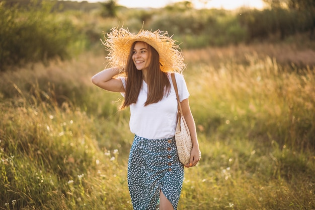 Young woman standing with bag in big hat in field