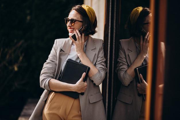 Giovane donna che sta con il libro all'aperto