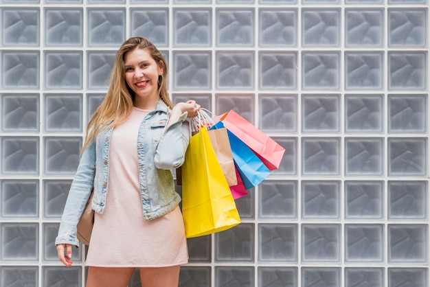 Молодая женщина, стоящая с яркими сумками