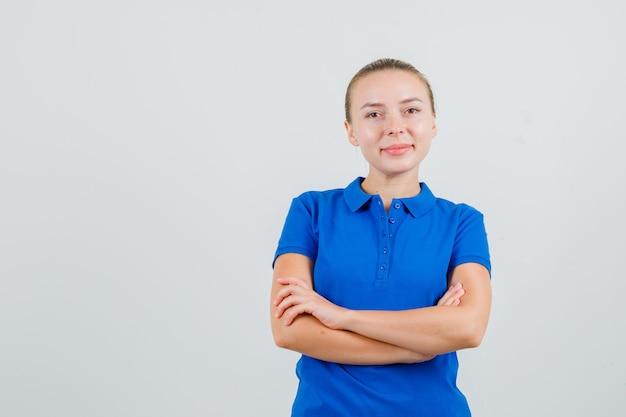 Giovane donna in piedi con le braccia incrociate in maglietta blu e guardando allegra