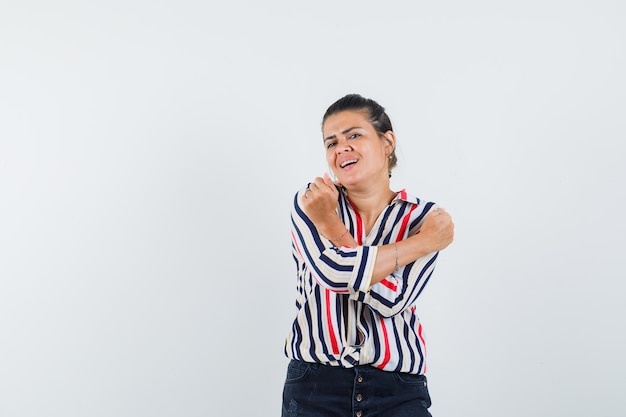 Young woman standing with crossed arms and clenching fists in striped blouse and looking optimistic