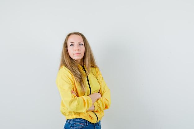 Молодая женщина, стоящая со скрещенными руками, замерзающая от холода в желтой куртке-бомбардировке и синих джинсах, выглядит уверенно. передний план.