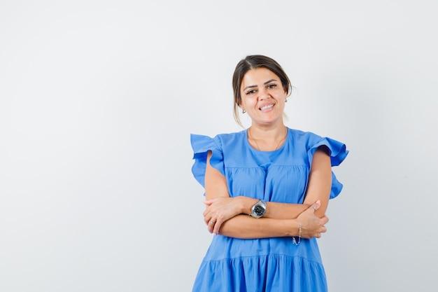 青いドレスを着て腕を組んで立って陽気に見える若い女性