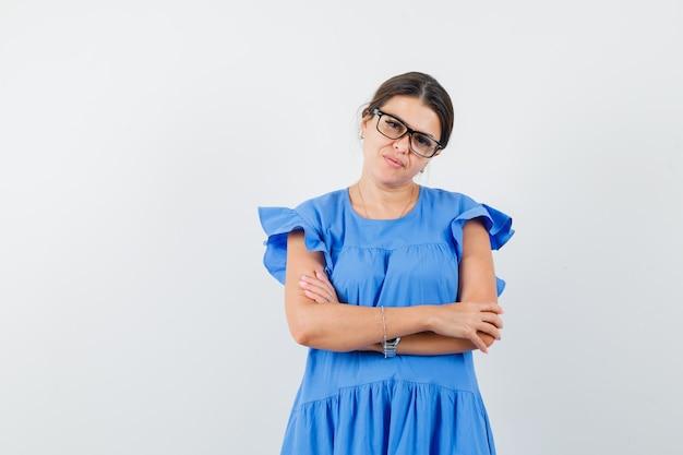 青いドレスを着て腕を組んで立っているとインテリジェントに見える若い女性