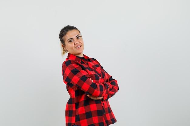 チェックシャツを着て腕を組んで立っている若い女性、自信を持って、正面図。
