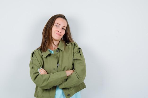 緑のジャケットで腕を組んで立って、自信を持って、正面図を探している若い女性。