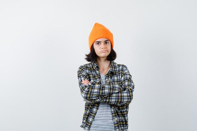 動揺して見えるオレンジ色の帽子の市松模様のシャツで腕を組んで立っている若い女性